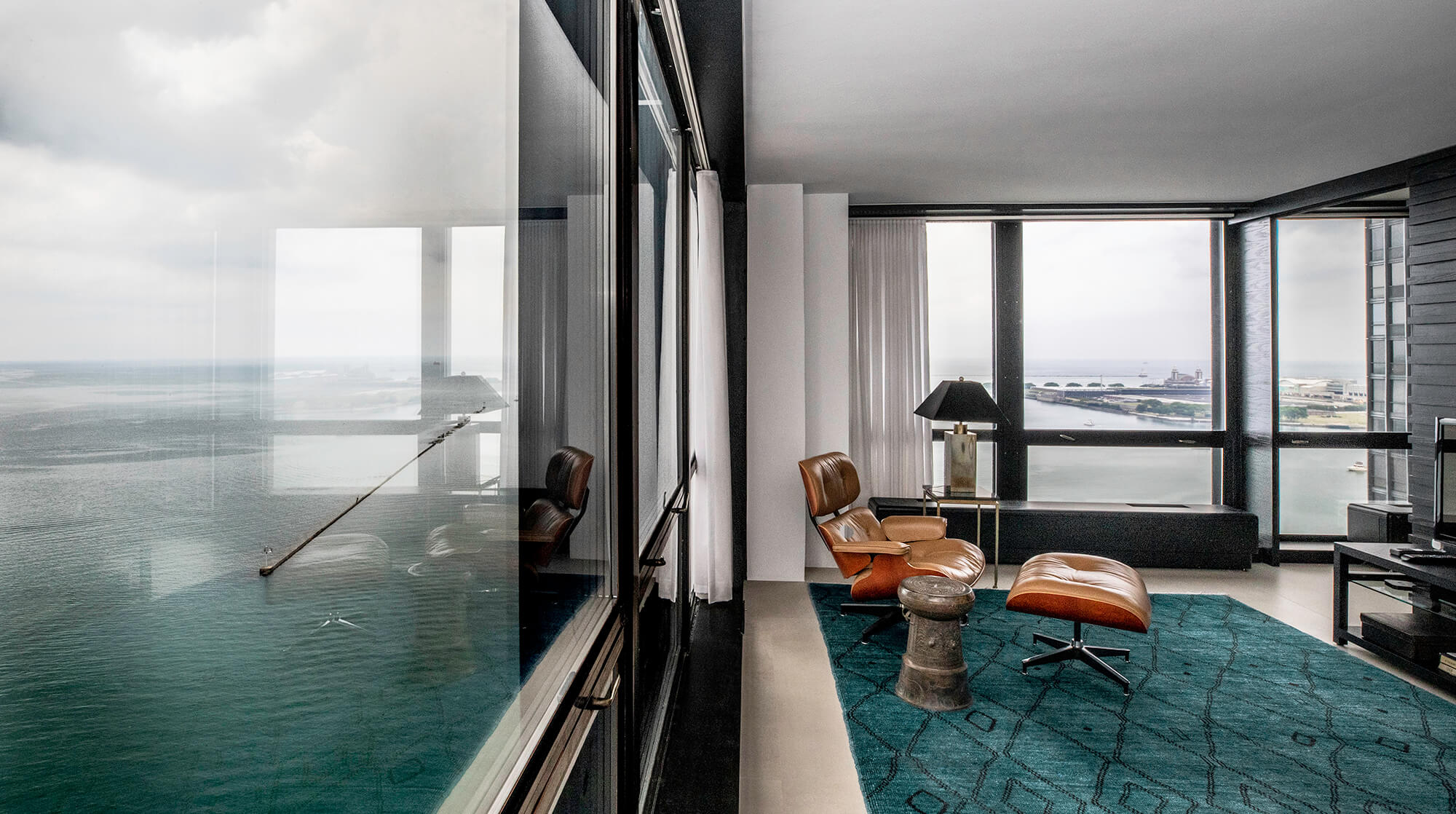 Photograph of condo room with view of Lake Michigan and mid century furniture